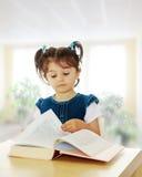 读书的小女孩在桌上 库存图片
