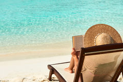 读书的少妇在海滩 免版税图库摄影