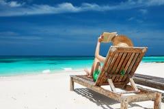 读书的少妇在海滩 免版税库存图片