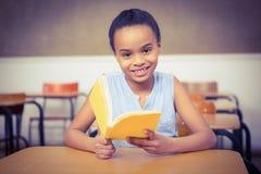 读书的微笑的学员 免版税图库摄影