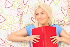 读书的快乐的女孩在床 免版税库存照片