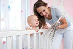 读书的愉快的妇女对一个逗人喜爱的婴孩 库存图片