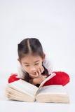 读书的愉快的逗人喜爱的女孩特写画象  免版税库存照片