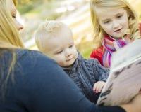 读书的母亲对她的两个可爱的白肤金发的孩子 免版税图库摄影