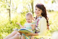 读书的母亲对她的孩子 免版税库存照片