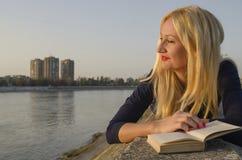 读书的白肤金发的妇女在河附近 库存图片