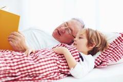 读书的祖父对他的孙在床上 库存图片