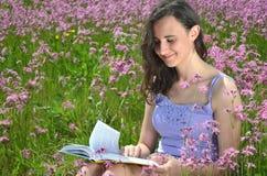 读书的美丽的可爱的深色的女孩在华美的草甸 免版税库存图片