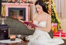 读书的美丽的女孩在圣诞夜 库存照片