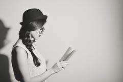 读书的美丽的女孩的黑白色图片反对轻的墙壁背景 免版税库存图片