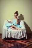 读书的美丽的女性坐在椅子反对轻的墙壁背景 库存照片