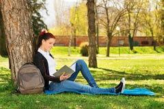 读书的美丽的微笑的学生 免版税图库摄影