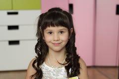 读书的美丽的愉快的小女孩 免版税图库摄影