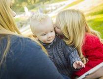读书的老师对两个可爱的白肤金发的孩子 免版税库存照片