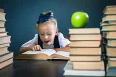 读书的聪明的学校女孩在图书馆 免版税图库摄影