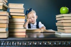 读书的聪明的学校女孩在图书馆 免版税库存图片