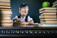 读书的聪明的学校女孩在图书馆 免版税库存照片