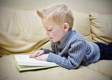 读书的逗人喜爱的男孩在长沙发 免版税库存图片