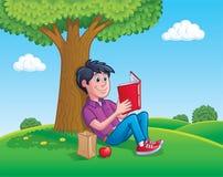 读书的青少年的男孩在树下 免版税库存照片