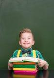 读书的滑稽的男孩在空的绿色黑板附近 免版税库存图片