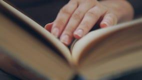 书的读者移动她的沿页的手指,当读时 股票视频