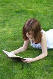 读书的Teen.Young美丽的女孩室外 免版税图库摄影