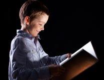 书被开张的男孩魔术 免版税图库摄影