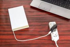 书被连接到电源输出口 免版税图库摄影