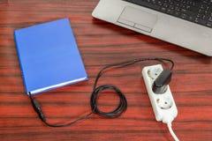 书被连接到电源输出口 免版税库存照片