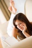 书读了松弛沙发妇女年轻人 免版税图库摄影