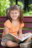 书逗人喜爱的女孩一点纵向微笑 免版税库存图片