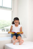 书逗人喜爱的女孩读取视窗 免版税库存图片