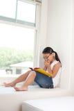书逗人喜爱的女孩读取 图库摄影