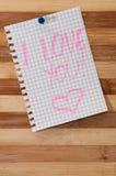 书面消息我爱你在作为背景的木板 库存图片