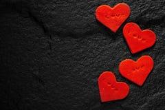 书面的红色心脏在黑石地板安置的爱词 免版税图库摄影