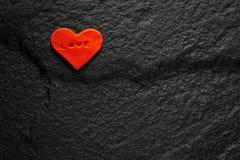 书面的红色心脏在黑石地板安置的爱词 库存图片