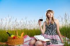 书饮用的女孩读取酒年轻人 免版税库存照片