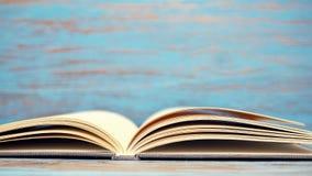 书&白色杯子在蓝色木背景 免版税库存照片