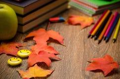 书 笔记本、铅笔、苹果计算机和秋叶在桌上 免版税库存图片