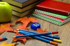 书 笔记本、铅笔、苹果计算机和秋叶在桌上 库存图片