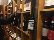 买一个瓶酒在超级市场 库存图片