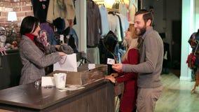 买一些衣物和支付与信用卡的美好的年轻夫妇 股票录像