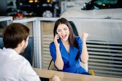 买一辆新的汽车的妇女谈话在智能手机 库存图片