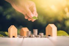 买与金钱硬币堆生长的一个房子或家庭储蓄概念的挽救 库存图片