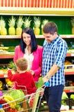 买健康食物的家庭在超级市场 库存图片