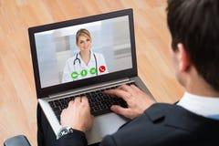 买卖人在网上Videochatting与On Laptop医生 免版税库存照片