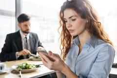 买卖人有工作午餐在坐的餐馆吃沙拉妇女特写镜头被集中的浏览智能手机 免版税图库摄影