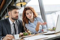 买卖人有工作午餐在坐的餐馆吃看膝上型计算机的沙拉饮用的浓咖啡 库存图片