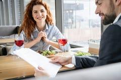 买卖人有工作午餐在坐的餐馆吃读文件的沙拉饮用的酒人,当妇女时 免版税库存照片