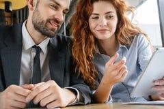 买卖人有工作午餐在坐的餐馆看数字片剂微笑 免版税库存图片